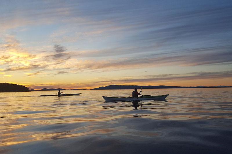 Sea Kayaking As The Sun Sets In San Juan Islands